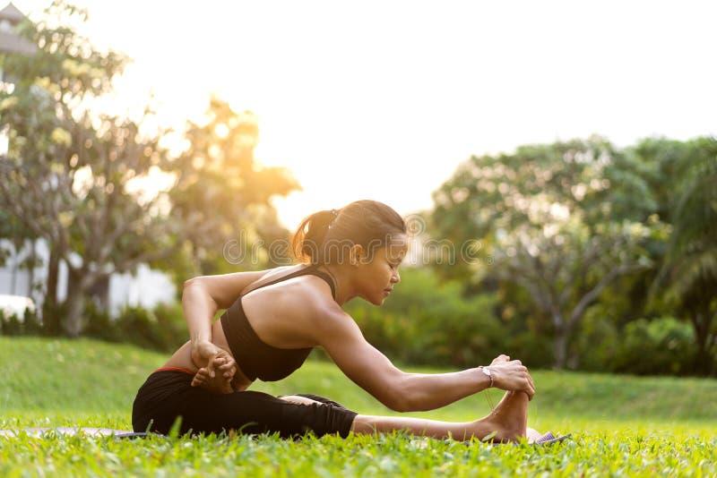 Flickan som gör yoga på solnedgången i Thailand i, parkerar arkivbild