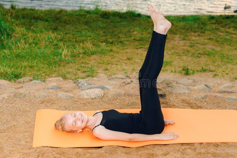 Flickan som gör yoga på solnedgången vid, rive royaltyfri fotografi