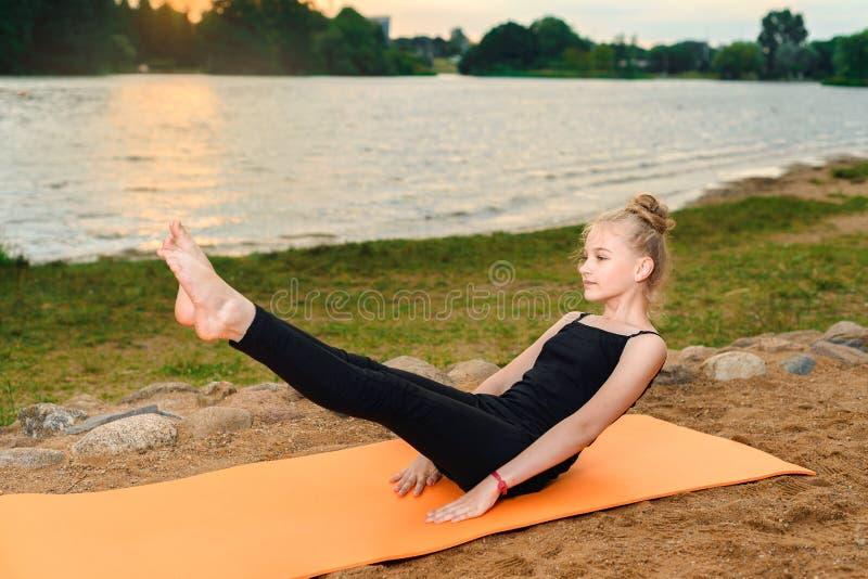 Flickan som gör yoga på solnedgången vid, rive royaltyfria bilder
