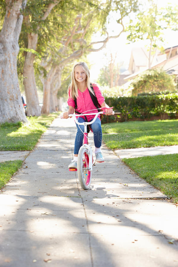Flickan som ha på sig ryggsäcken som cyklar till, skolar royaltyfria foton