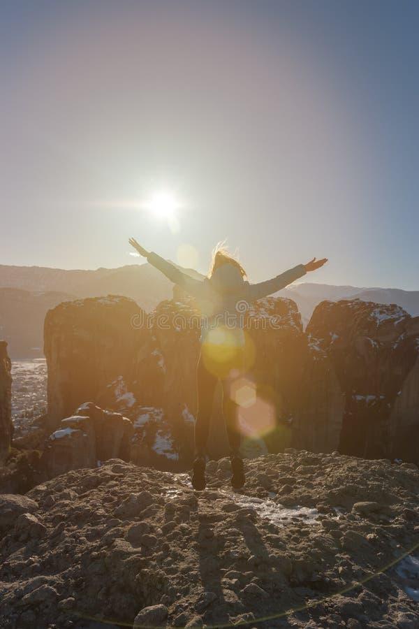 Flickan som handelsresanden hoppar högt på, vaggar av den Meteora kloster i Grekland på en ljus solig dag royaltyfri bild