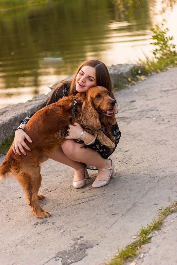 Flickan som kramar bokslut för closeup för gullig förtjusande röd hund för hundhusdjur vänligt, synar roliga djur royaltyfri bild