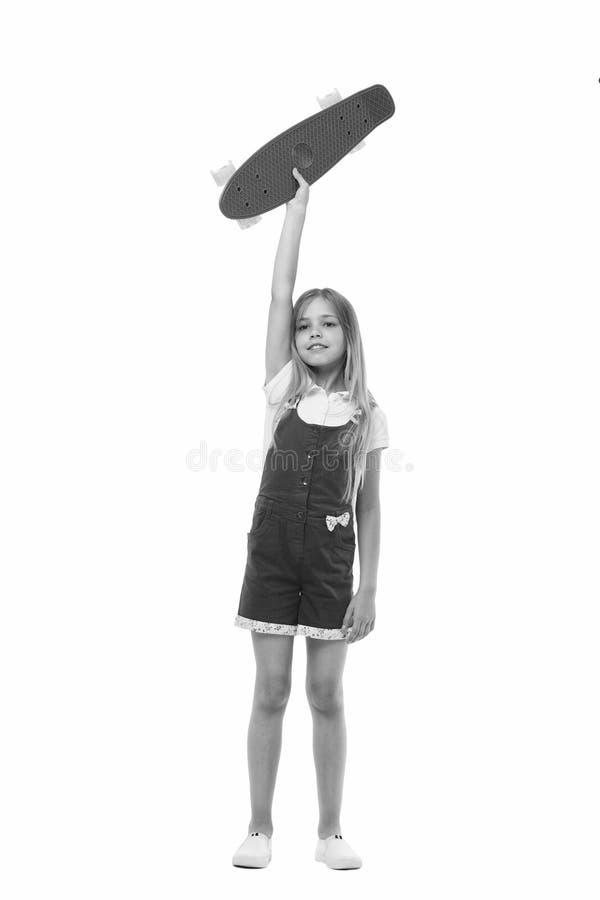 Flickan som ler brädet för framsidahållencentmyntet, isolerade vit bakgrund Ungeflicka med långt hår som är klart att rida encent arkivfoton