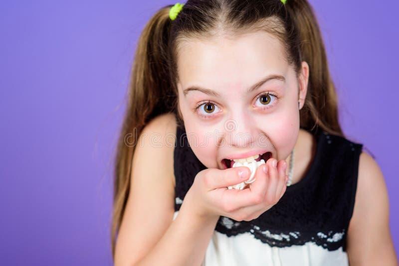 Flickan som ler framsidan, rymmer söta marshmallower i violett bakgrund för handen Gottegrisbegrepp Ungeflicka med långa hårnågot arkivbilder