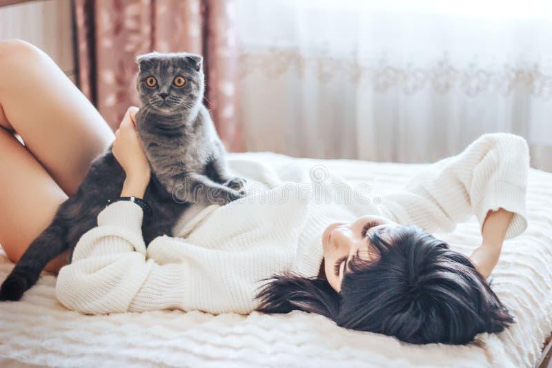 Flickan som ligger på säng med katthusdjur, komfort, vilar och folkbegreppet - lycklig ung kvinna med katten som hemma ligger i s royaltyfri foto