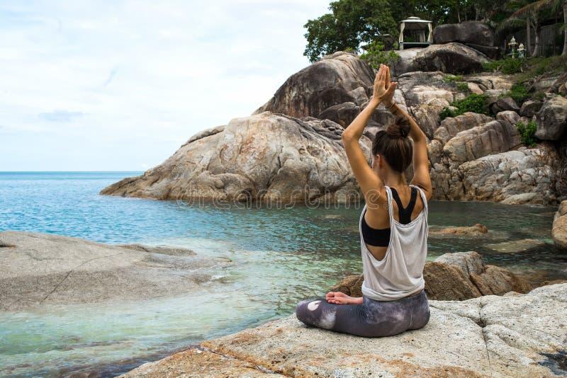 Flickan som mediterar på stenar vid havet, flickalånet med yoga ön Samui, yoga i Thailand arkivbild