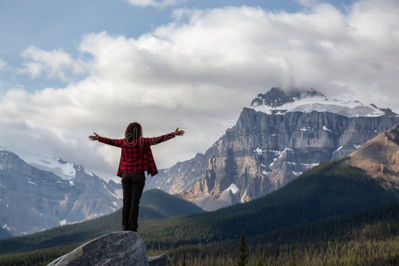 Flickan som njuter av den vackra scenen i Kanadas Rockies royaltyfri bild