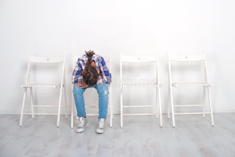 Flickan som placerar p? en vit stol med hans huvud ner Hon ?r n?got uppriven och k?nslom?ssigt f?rargad arkivfoton