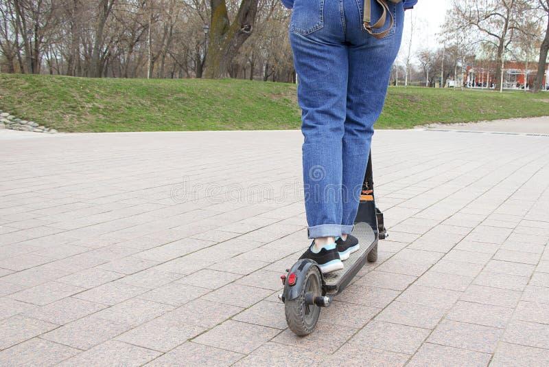 Flickan som rider en elektrisk sparkcykel i, parkerar r Modern aktiv livsstil arkivbilder