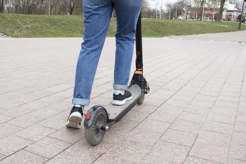 Flickan som rider en elektrisk sparkcykel i, parkerar vägen r Modern aktiv livsstil royaltyfri fotografi