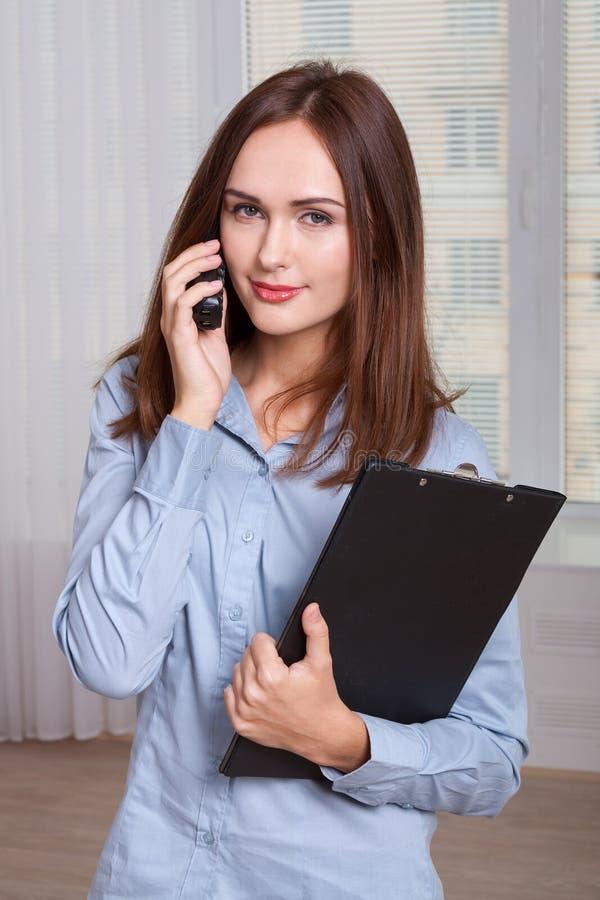 Flickan som rymmer en mapp och, talar vid telefonen royaltyfri bild