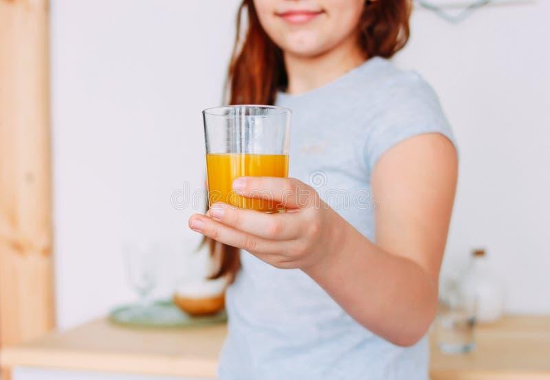 Flickan som rymmer exponeringsglas av orange fruktsaft i handen, selektiv fokus royaltyfri bild