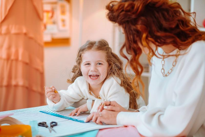 Flickan som skrattar framställning, skissar med mamman som arbetar som formgivare fotografering för bildbyråer