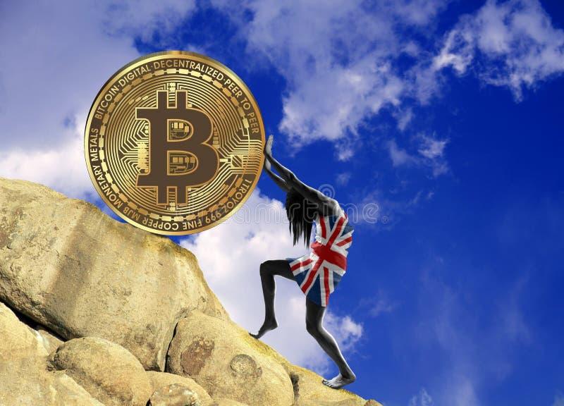 Flickan som slås in i en flagga av Storbritannien, lyfter ett bitcoinmynt upp kullen royaltyfri bild