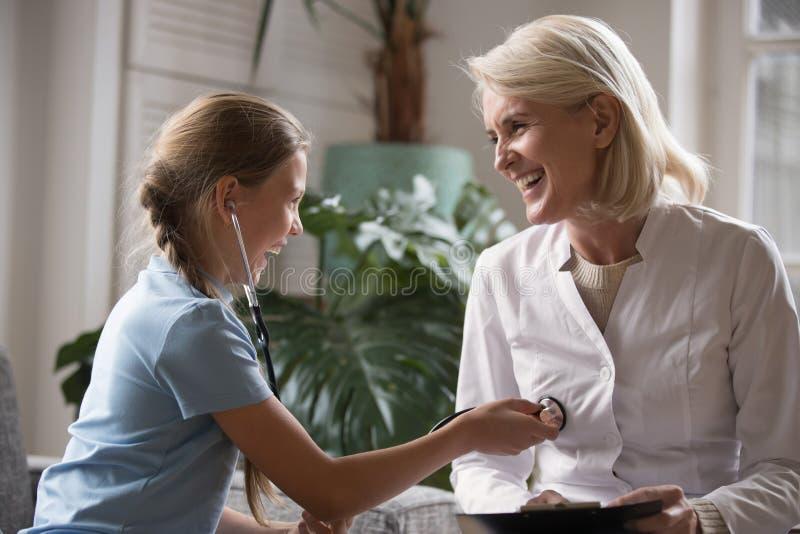 Flickan som spelar som doktorn som använder stetoskopet, lyssnar hjärtslaget av pediatriskt arkivfoton