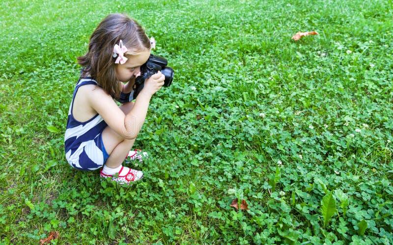 Flickan, som tar, bilder med en fotokamera parkerar in royaltyfria bilder