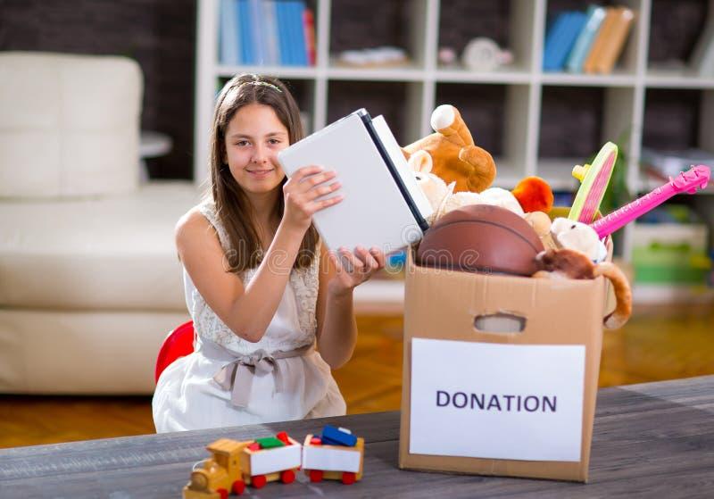 Flickan som tar donationasken med material för, donerar mycket royaltyfria bilder