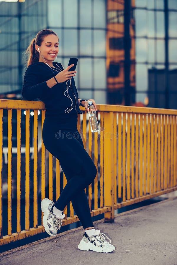 Flickan som tar ett avbrott efter, utarbetar och lyssnande musik, medan genom att använda den smarta telefonen royaltyfri foto