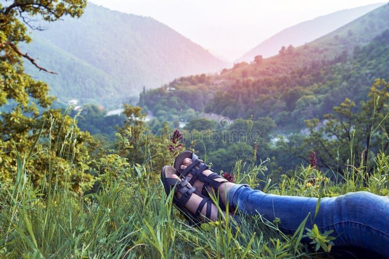 Flickan som tycker om sommar, vilar ilying på grönt gräs i berg royaltyfri bild