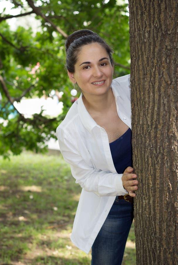 Flickan som ut ser på grund av ett träd arkivbild