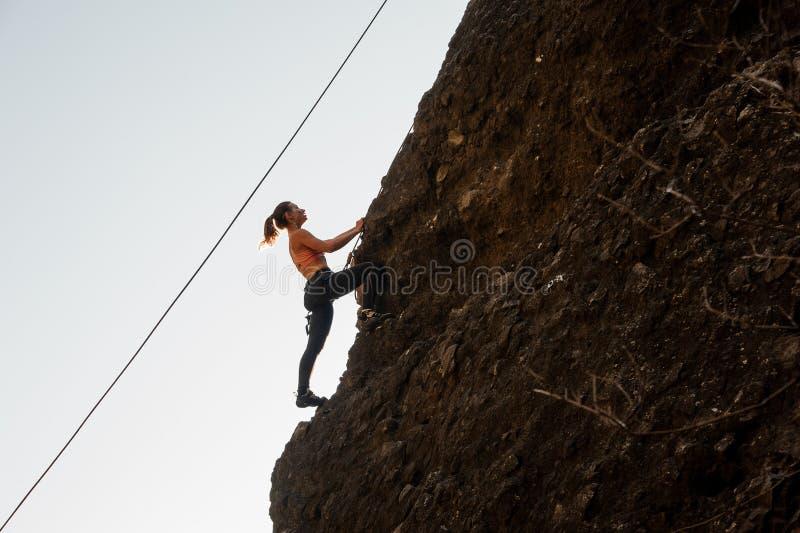 Flickan som utrustas med ett rep som klättrar på slutta, vaggar royaltyfri foto