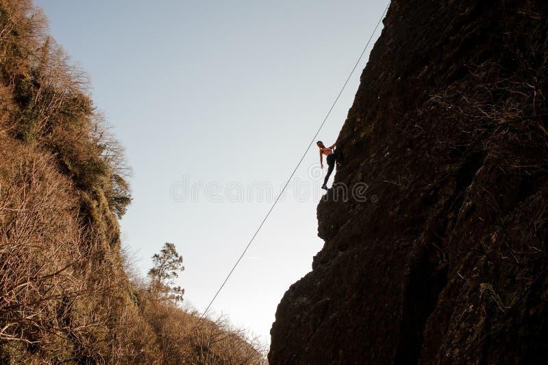 Flickan som utrustas med ett rep som klättrar på slutta, vaggar och att se tillbaka royaltyfria bilder