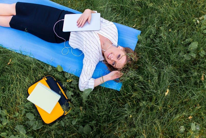 Flickan som vilar i, parkerar att ligga p? gr?set med en b?rbar dator och att lyssna till musik B?sta wiew royaltyfria foton