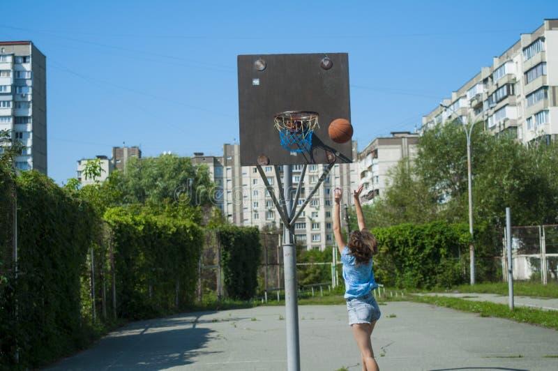 Flickan spelar basket på gatan arkivfoton