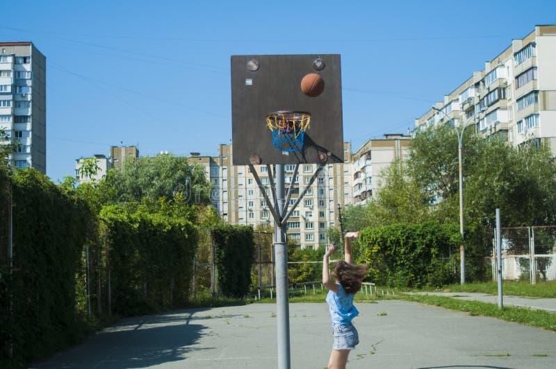 Flickan spelar basket på gatan Kastar bollen in i korgen royaltyfria bilder