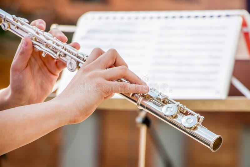 Flickan spelar flöjten Blåsa flöjt i händerna av musikerduren royaltyfri foto