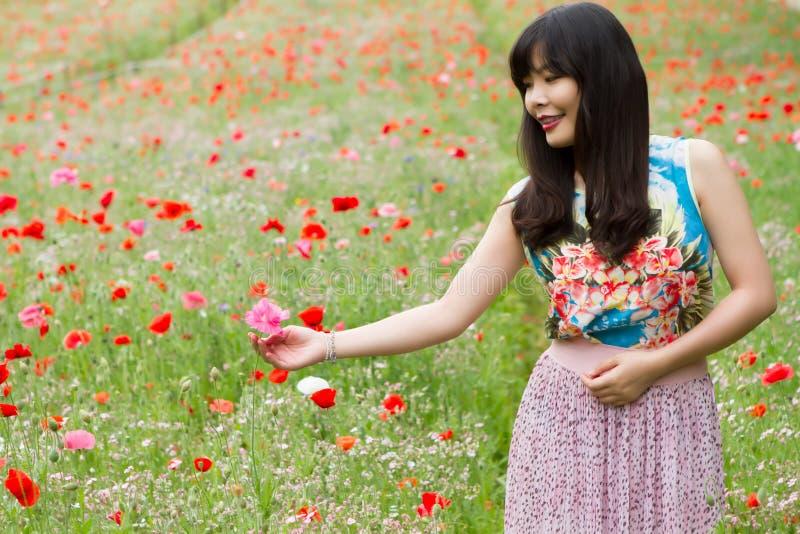 Flickan spelar med en blomma i vallmofält royaltyfri fotografi