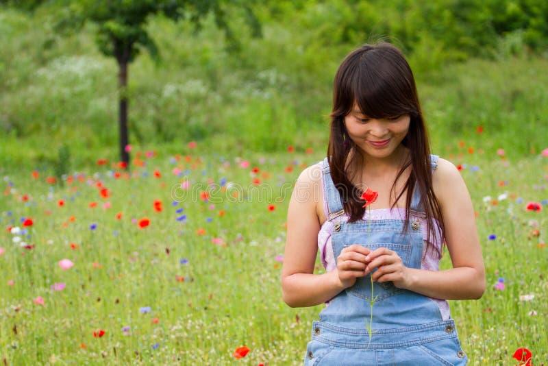 Flickan spelar med en blomma i vallmofält arkivbild