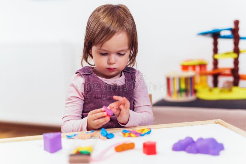 Flickan spelar med plasticine, medan sitta på tabellen i barnkammarerum, selektiv fokus fotografering för bildbyråer