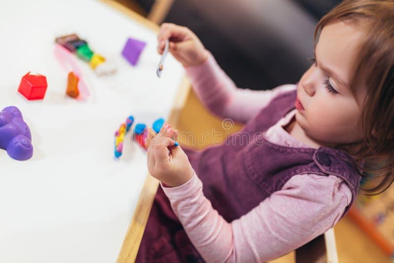 Flickan spelar med plasticine, medan sitta på tabellen i barnkammarerum, selektiv fokus arkivfoton