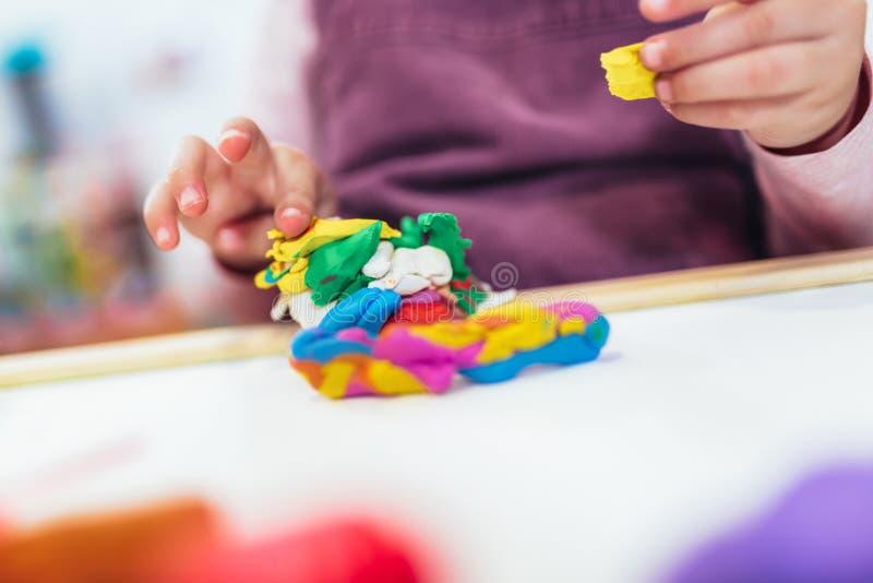 Flickan spelar med plasticine, medan sitta på tabellen i barnkammarerum, selektiv fokus arkivbilder