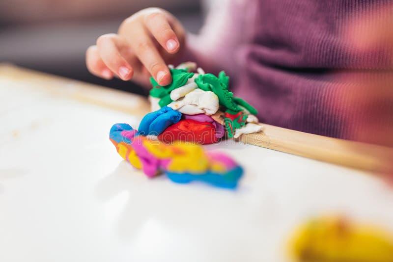Flickan spelar med plasticine, medan sitta på tabellen i barnkammarerum, selektiv fokus royaltyfria bilder