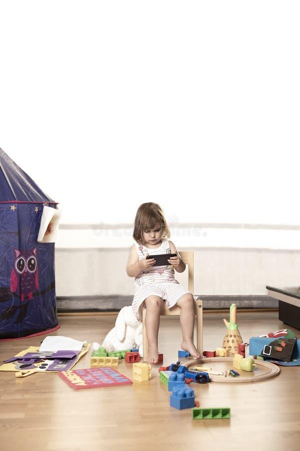 Flickan spelar mobiltelefonen Flickan hakas till mobiltelefonen Han spelar inte med leksaker Mobiltelefonen är dålig för barn royaltyfria foton