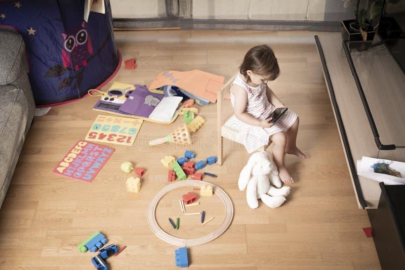 Flickan spelar mobiltelefonen Flickan hakas till mobiltelefonen Han spelar inte med leksaker Mobiltelefonen är dålig för barn royaltyfria bilder