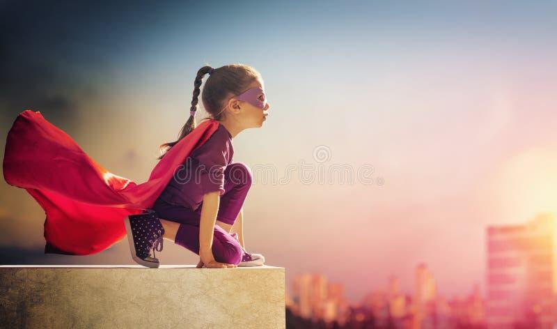 Flickan spelar superheroen royaltyfri fotografi