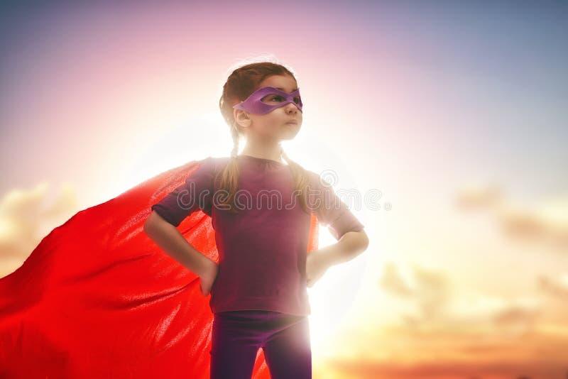Flickan spelar superheroen arkivbild