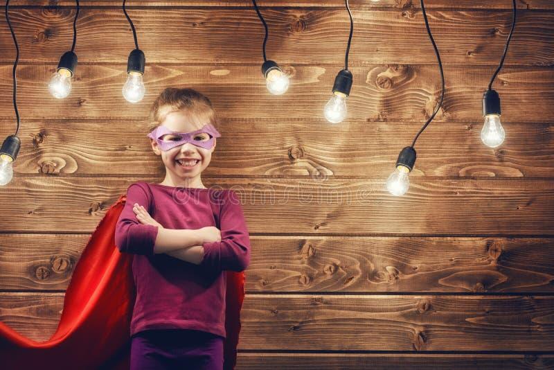 Flickan spelar superheroen arkivbilder