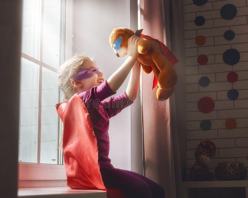 Flickan spelar superheroen fotografering för bildbyråer