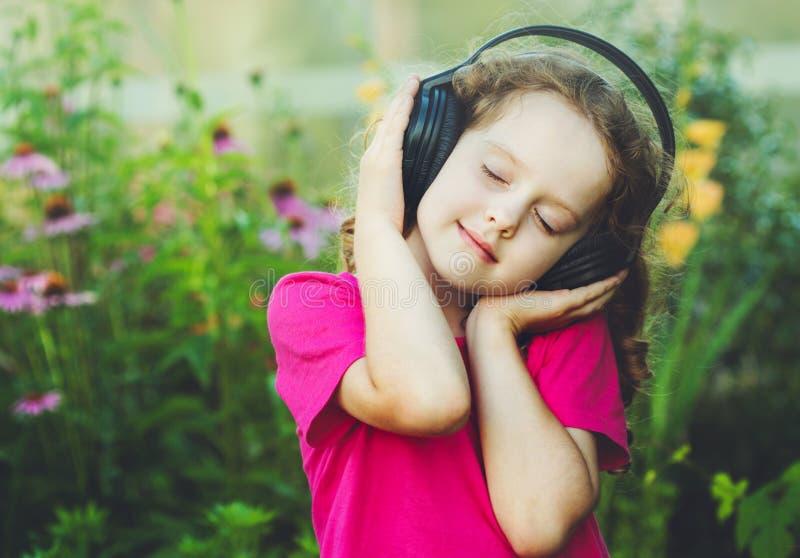 Flickan stängde henne ögon och lyssnar till musik på hörlurar Instagra royaltyfri bild