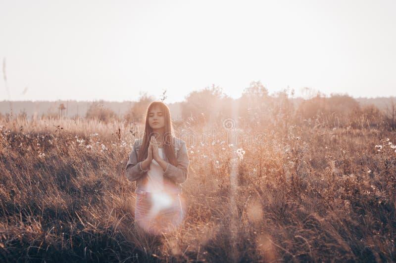Flickan stängde henne ögon som utomhus ber, händer vikta i bönbegreppet för tro, andlighet och religionen hopp drömbegrepp royaltyfri bild