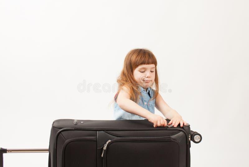 Flickan stänger resväskan på vit bakgrund arkivfoto