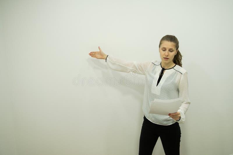 Flickan står av den vita väggen och ställningarna som tappar hennes ögon till rapporten som rymmer en rapport i en hand som indik arkivfoto