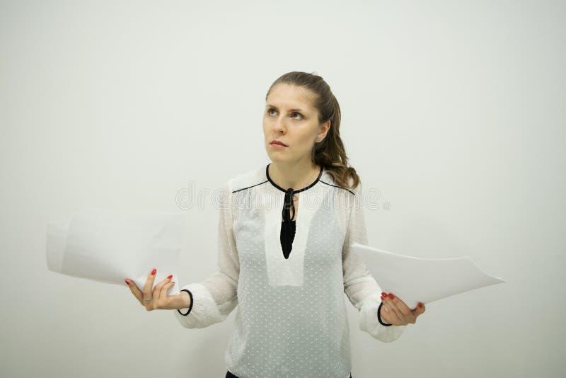 Flickan står displeasedly till midjan, medan rymma tomma ark av papper med hoprullade ögon i båda händer arkivbild