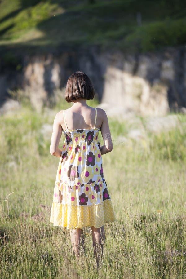 Flickan står i en äng royaltyfria foton