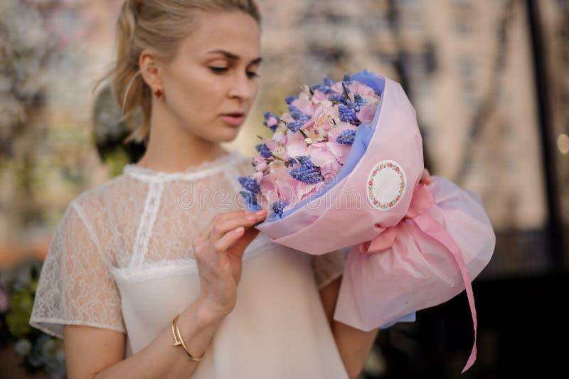 Flickan står med buketten av rosa och blåa blommor royaltyfri foto