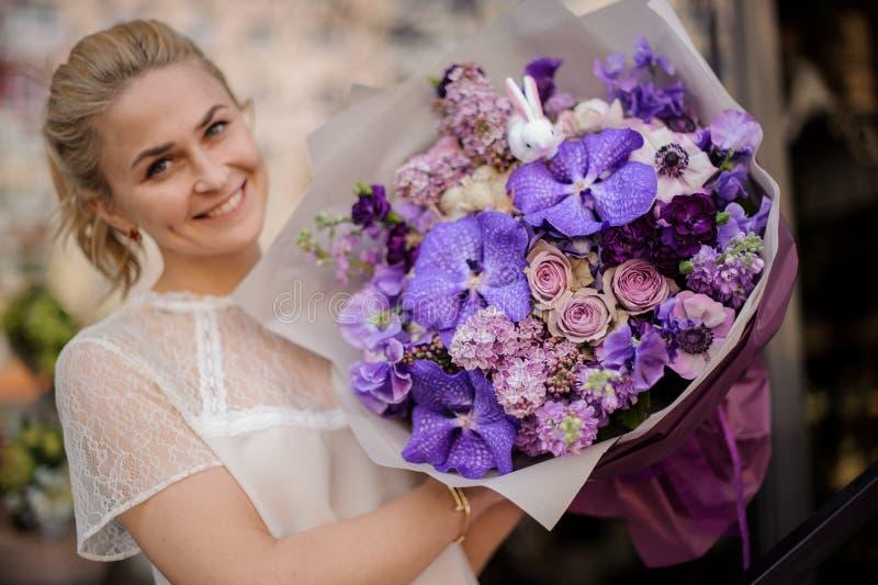 Flickan står med en fullständigt purpurfärgad bukett royaltyfria bilder